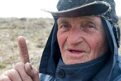 Portrait d'un vieil homme dans les v?tements et le chapeau malpropres qui ont soulev? son index, j'ai une id?e photographie stock libre de droits