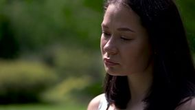 Portrait d'un visage asiatique triste de fille Arbres verts sur le fond Larmes roulant vers le bas la joue Fin vers le haut banque de vidéos