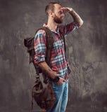 Portrait d'un voyageur tatoué beau dans une chemise de flanelle avec un sac à dos, se tenant dans un studio images libres de droits