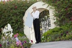 Portrait d'un vrai agent immobilier femelle supérieur tenant le panneau de signe devant la porte d'entrée Photos libres de droits
