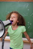 Portrait d'une écolière mignonne criant par un mégaphone Image stock