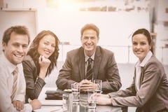Portrait d'une équipe positive s'asseyant à une table Photos stock
