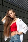Portrait d'une adolescente dans la rue près d'un mur gris Photographie stock libre de droits