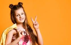 Portrait d'une adolescente mignonne, charmante, attirante, gaie, montrant un V-signe sur un fond jaune et tenant une veste photographie stock