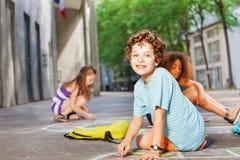 Portrait d'une aspiration de garçon avec des amis sur la rue Photographie stock
