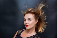 Portrait d'une belle femme avec de beaux cheveux sur un fond foncé photo stock