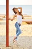 Portrait d'une belle femme avec les cheveux magnifiques dans un dessus blanc et des jeans élégants Images stock