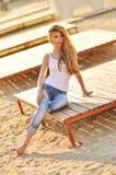 Portrait d'une belle femme avec les cheveux magnifiques dans un dessus blanc et des jeans élégants Photographie stock libre de droits