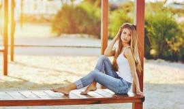 Portrait d'une belle femme avec les cheveux magnifiques dans un dessus blanc et des jeans élégants Image stock