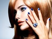 Portrait d'une belle femme avec les clous bleus, maquillage bleu photo libre de droits