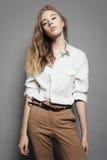 Portrait d'une belle femme blonde dans une chemise blanche dans le studio sur un fond gris Photo libre de droits