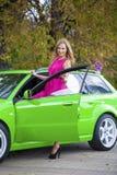 Portrait d'une belle femme blonde et d'une voiture de sport verte images libres de droits