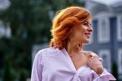Portrait d'une belle femme d'une cinquantaine d'années de sourire avec les cheveux rouges un jour nuageux images stock