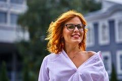 Portrait d'une belle femme d'une cinquantaine d'années de sourire avec les verres de port de cheveux rouges un jour nuageux photo stock