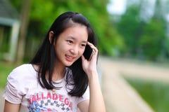 Portrait d'une belle femme dactylographiant au téléphone intelligent dans un pair photos stock