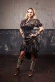 Portrait d'une belle femme de steampunk dans le chemisier rayé luxuriant, au-dessus du fond grunge Photos stock