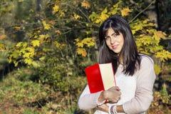 Portrait d'une belle femme en parc d'automne, tenant un livre image libre de droits