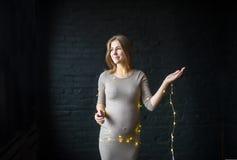 Portrait d'une belle femme enceinte avec l'illumination dans le studio sur un fond noir de brique image libre de droits