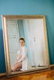 Portrait d'une belle femme enceinte devant un miroir à la maison photos stock