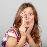 Portrait d'une belle femme gaie avec la sucrerie tricotée dans des mains Fin femelle de visage sur le fond gris photos stock