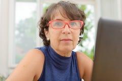 Portrait d'une belle femme mûre avec les verres rouges Photographie stock libre de droits