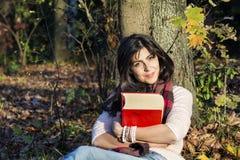 Portrait d'une belle femme se penchant sur un arbre avec le livre en parc d'automne Photos stock