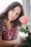 Portrait d'une belle femme sur le fond clair dans les roses roses Images stock