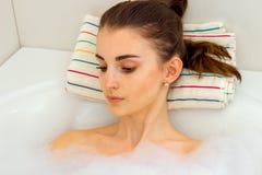 Portrait d'une belle fille avec les cheveux foncés qui sont dans l'eau dans la salle de bains et ont abaissé ses yeux vers le bas Photos libres de droits
