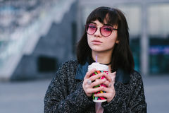 Portrait d'une belle fille avec les verres roses et lumineux élégants avec une tasse de café à disposition Images stock