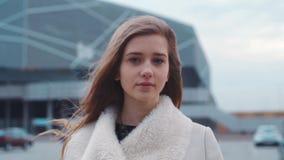 Portrait d'une belle fille blonde marchant par le stationnement et regardant à l'appareil-photo par temps nuageux venteux et banque de vidéos