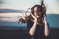 Portrait d'une belle fille dans des écouteurs écoutant la musique sur la nature photo stock