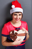 Portrait d'une belle fille dans des chapeaux de Santa avec le boîte-cadeau Photo stock