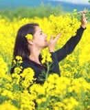 Portrait d'une belle fille dans le domaine de colza en été Photographie stock libre de droits