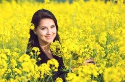 Portrait d'une belle fille dans le domaine de colza en été Photos stock