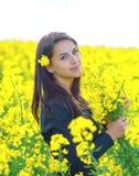 Portrait d'une belle fille dans le domaine de colza en été Image stock