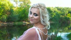 Portrait d'une belle fille dans une robe rose dans un domaine avec le maquillage au coucher du soleil en été clips vidéos