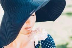 Portrait d'une belle fille dans un chapeau et une rose dans des ses mains Photographie stock