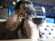 Portrait d'une belle fille de brune s'asseyant à la table avec un verre de vin rouge images stock