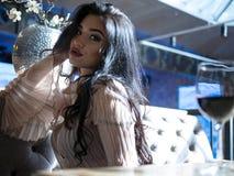 Portrait d'une belle fille de brune s'asseyant à la table avec un verre de vin rouge photo stock