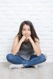 Portrait d'une belle fille de sourire heureuse s'asseyant sur le plancher image libre de droits