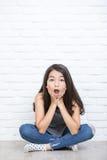 Portrait d'une belle fille de surprise s'asseyant sur le plancher Photographie stock
