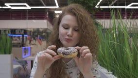 Portrait d'une belle fille heureuse avec les cheveux rouges mangeant un beignet, regardant la caméra banque de vidéos
