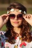 Portrait d'une belle fille hippie qui remet tenir des lunettes de soleil dehors Images libres de droits