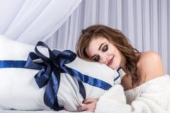 Portrait d'une belle fille modèle dans un chandail tricoté sur un lit blanc La tête de la blonde se trouve sur un oreiller avec u Photos stock