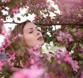 Portrait d'une belle fille parmi le feuillage et les fleurs de ressort images libres de droits