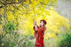 Portrait d'une belle fille parmi les fleurs jaunes dans la nature Photos stock