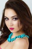 Portrait d'une belle fille réfléchie avec le collier bleu Photo stock