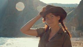 Portrait d'une belle fille rousse de voyageur dans un chapeau de cowboy sur la plage de mer banque de vidéos