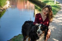 Portrait d'une belle fille s'accroupissant avec son chien par un courant images stock