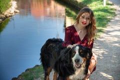 Portrait d'une belle fille s'accroupissant avec son chien par un courant photo libre de droits